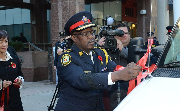 Man in a police uniform tying a red ribbon to the police car antenna
