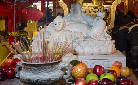 Incense and apples near a statue of Buddha