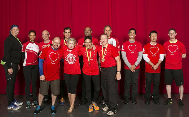 A group of men and women, mostly wearing red T-shirts stand together