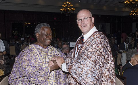 Two men wearing long multi-coloured robes
