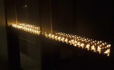 Rows of tea lights along a window ledge