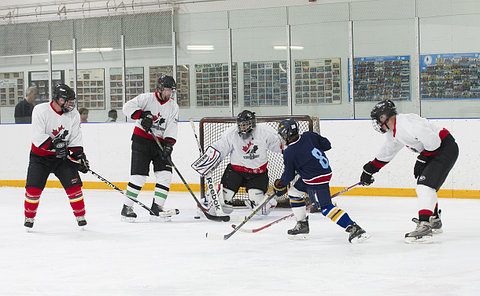 A boy shoots a puck at a goalie