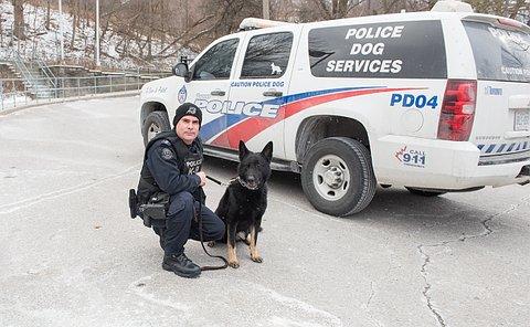 A man in TPS uniform kneels beside a German Shepherd and a TPS SUV