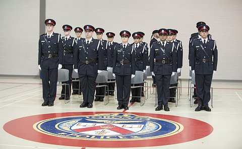 Men and women in TPS uniform in front of a TPS logo on the ground