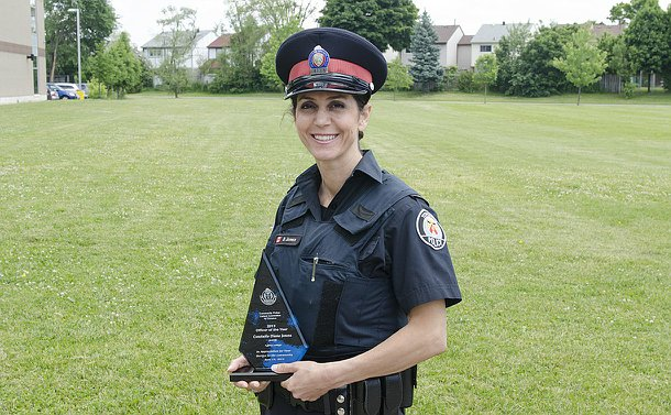 A woman in TPS uniform holds a glass award