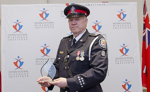 Man in a police uniform holding an award statue made of glass