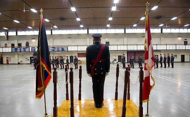 A man in Ceremonial Unit uniform standing at a podium looking towards the Unit in parade. His back is turned to the camera.