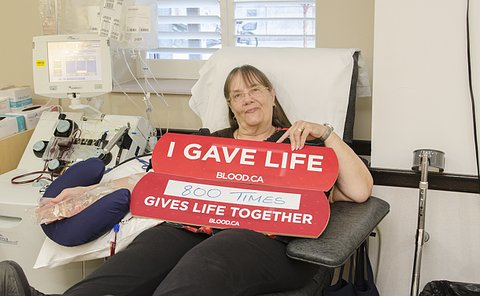 A woman beside medical equipment with a sign that says: I gave life 800 times