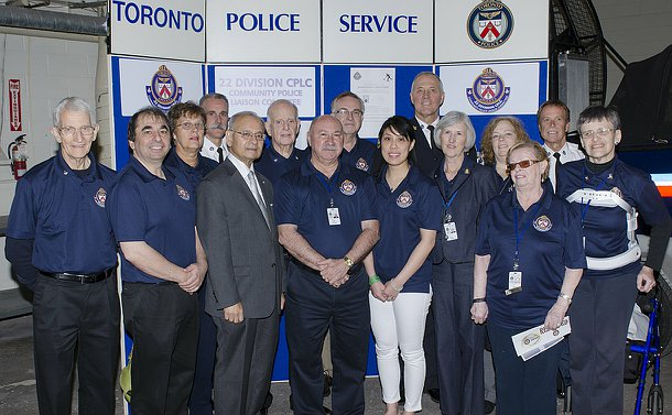 A group of men and women in blue golf shirts with men in TPS uniform and one man in a suit against a Toronto Police display board