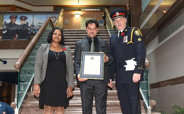 A woman with a man holding a framed certificate and a man in TPS uniform