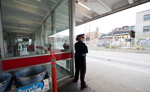 An officer standing at a bus bay.