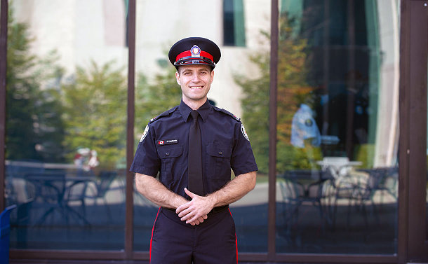 Man in police uniform stands in front of a glass building