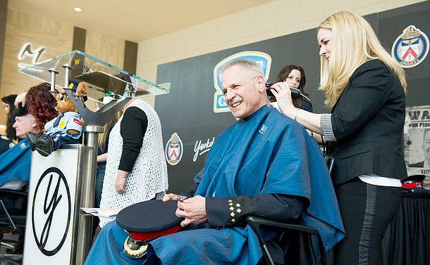 A officer sitting on stage in a chair getting his head shaved and smiling