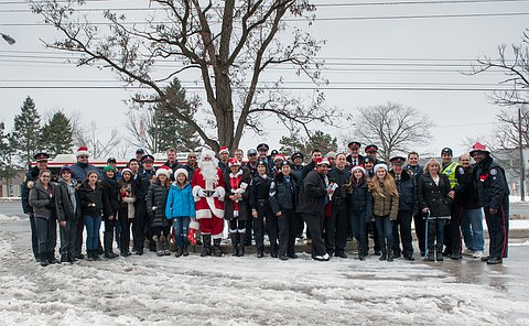 A large group of people, many in TPS police and auxiliary uniform standing on a snowy bank