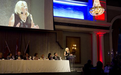 A blonde-haired woman speaks at a podium in a ballroom beside a head table and is projected on a large screen above her