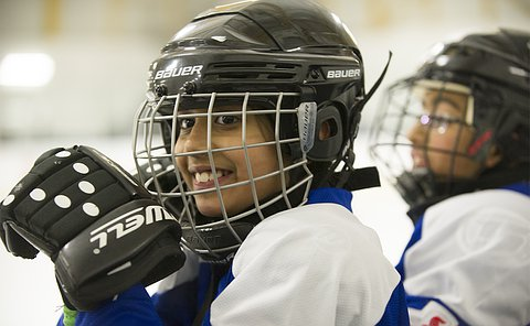 A close up of girl in a hockey helmet, mask and uniform smiling