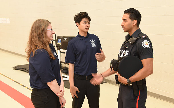 Two teenagers speaking to a man in TPS uniform