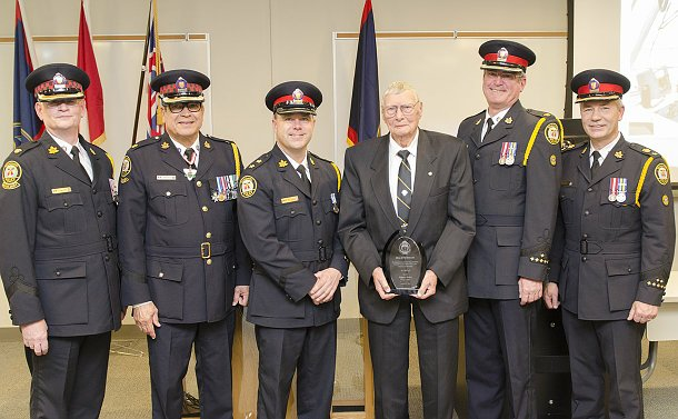 Men in Auxiliary and Police uniform with another man holding an award