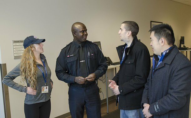 A man in TPS uniform speaks to a woman and two men