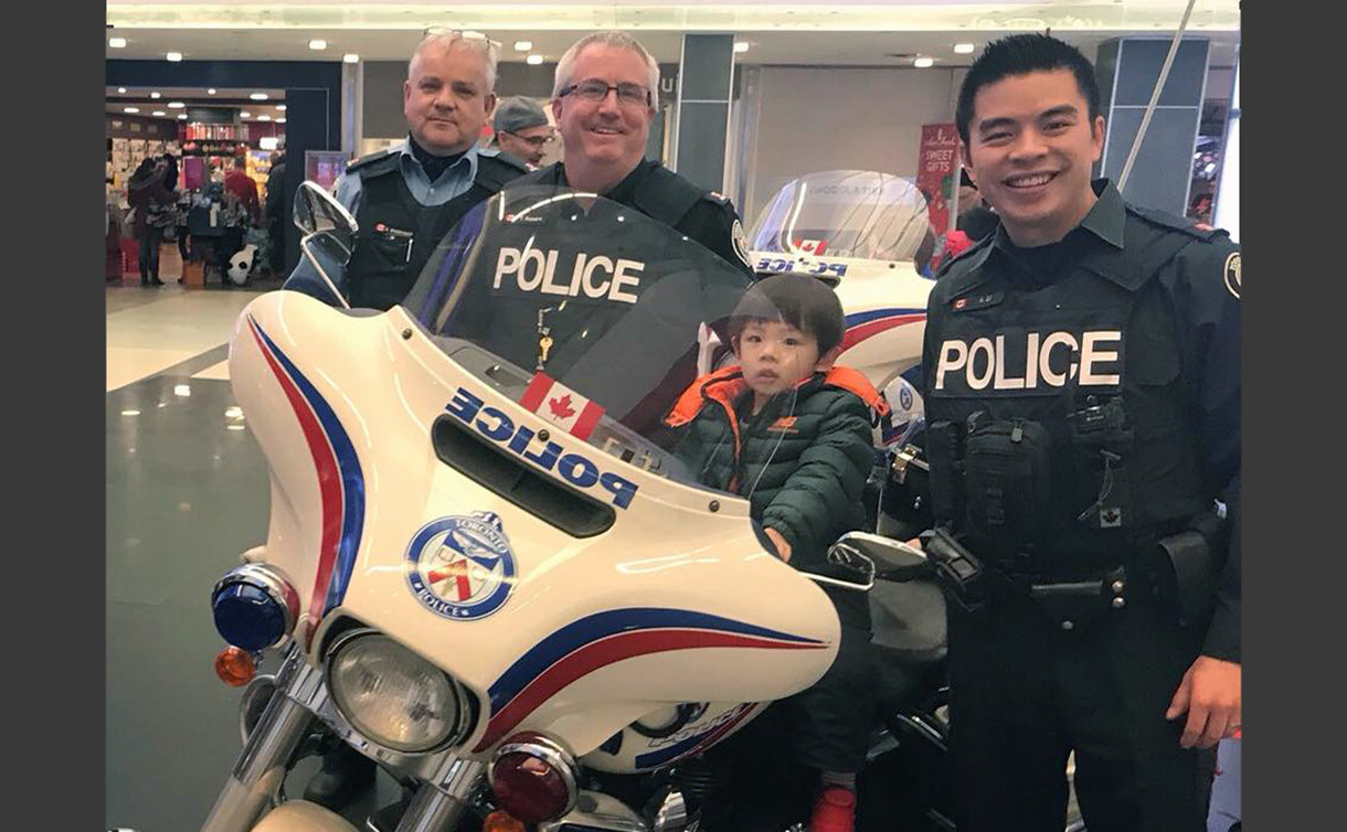 TPS officers with a boy on a motorcycle