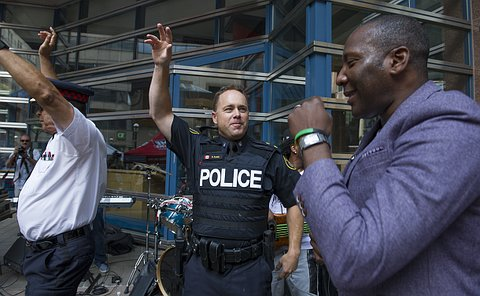 A man sings into a microphone with two men in TPS uniform waving hands