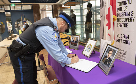 A man in TPS court uniform at a table with a book and framed photos