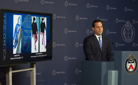 A man at a podium beside a TV with photos of two men
