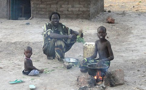 A woman hunched over a fire as two children on both sides of her look on