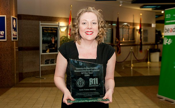 A woman in a black dress, holding a glass shield award.