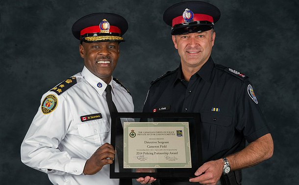 Two men in TPS uniform holding an award