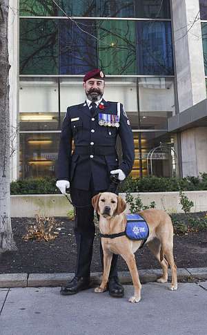 A man in TPS uniform with a dog in a vest