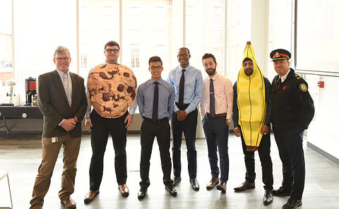 Men standing together, one dressed as cookie, another as a banana