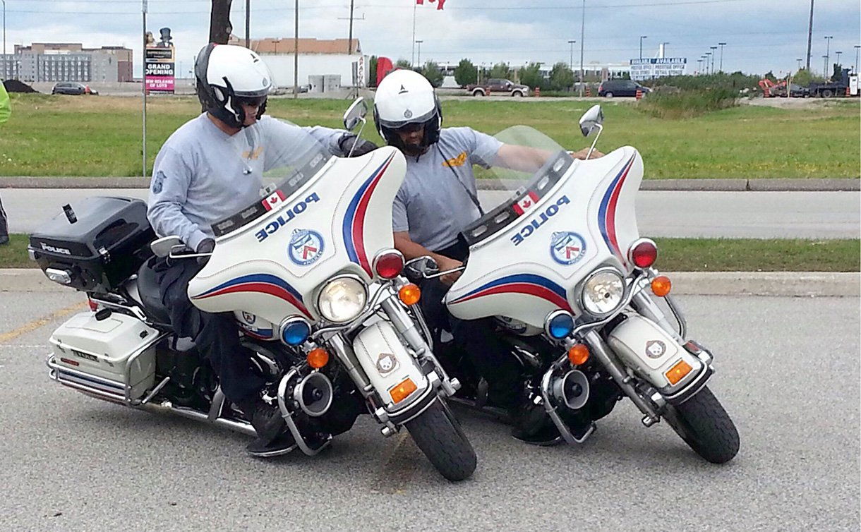 Two men in TPS uniform and atop TPS motorcycles ride in the same direction making a turn inches apart