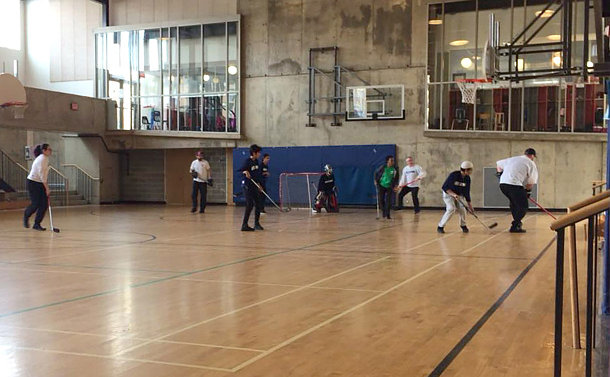 A group of people playing floor hockey in a gym