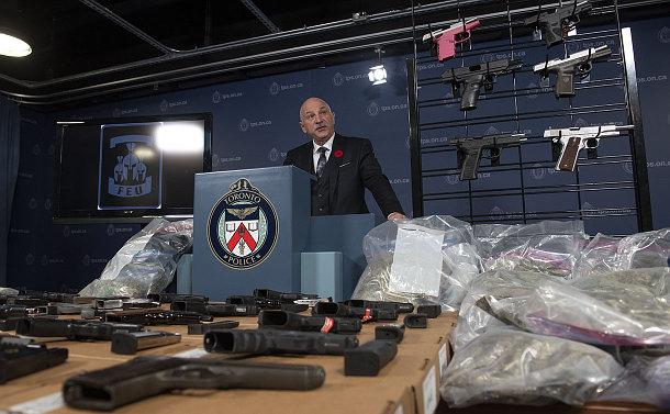 A man at a podium behind a table of guns
