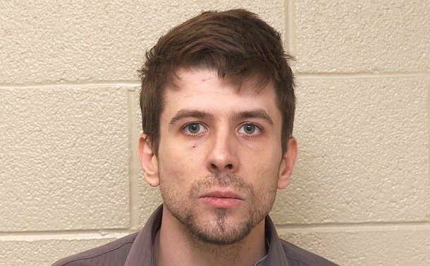 A headshot of a man against a wall