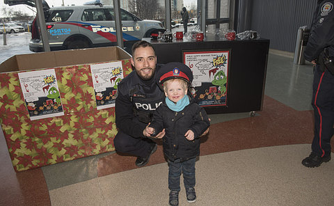 A man in TPS uniform with a boy wearing his TPS hat