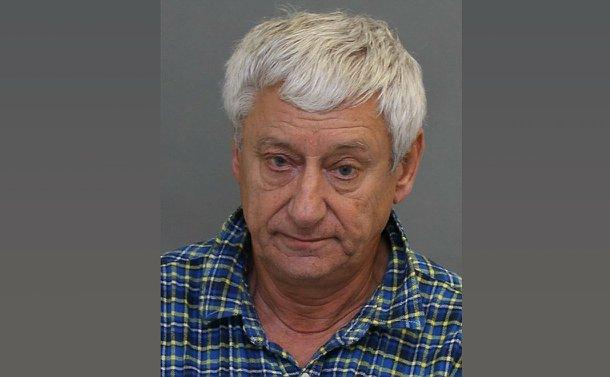 A mug shot of an elderly man in a plaid shirt.