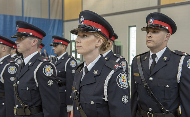 One woman and a group of men, all wearing police uniforms, standing at attention