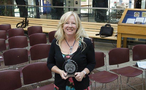 A woman holding an award