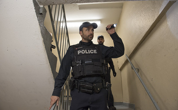 A man in TPS uniform holding a flashlight on a set of stairs