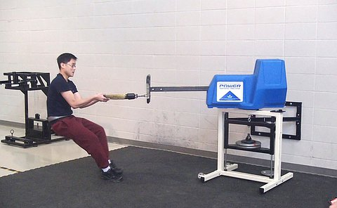 A teenage boy leans back against a exercise-style machine