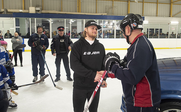 A man shakes hands with a man on a rink