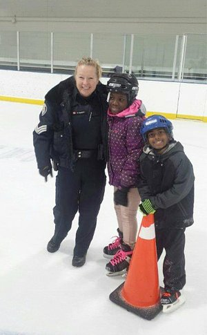 A woman in TPS uniform beside a boy and girl on an ice rink