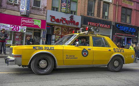 A man in TPS auxiliary uniform drives a yellow police scout car