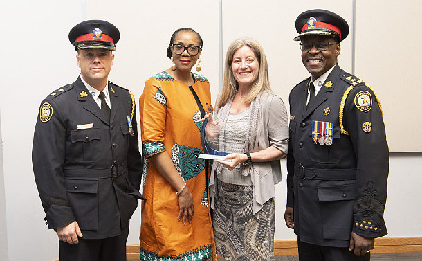 Two women in the middle are flanked by two men who are wearing a police uniform