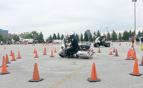 A man in TPS uniform on a TPS motorcycle turns surrounded by a circle of pylons