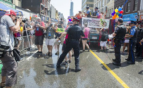 TPS Officers getting splashed with water from the crowd at the 2014 World Pride Parade.