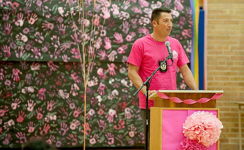 a man in a pink shirt standing at a podium speaking.