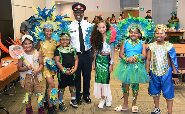 A man in a police uniform stands among children dressed in carnival costumes